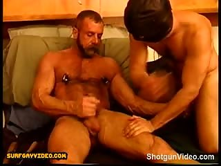 Two muscle studs have a mutual ball squeezing and punching session as they jack off two big cocks.