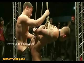 Gay boy tied in leather leash fucked in the mouth in middle of group of men